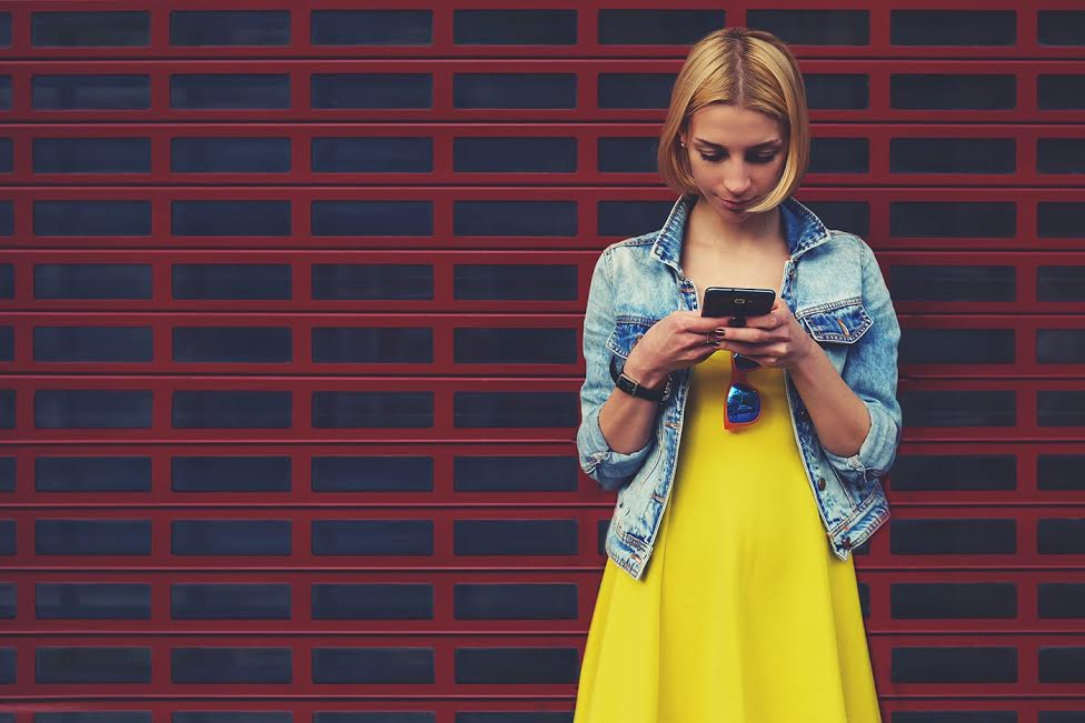 Pretty young woman chatting on her smartphone against blank copy space bright background for your content or text message,female hipster student in the dress using mobile phone for connect to wireless