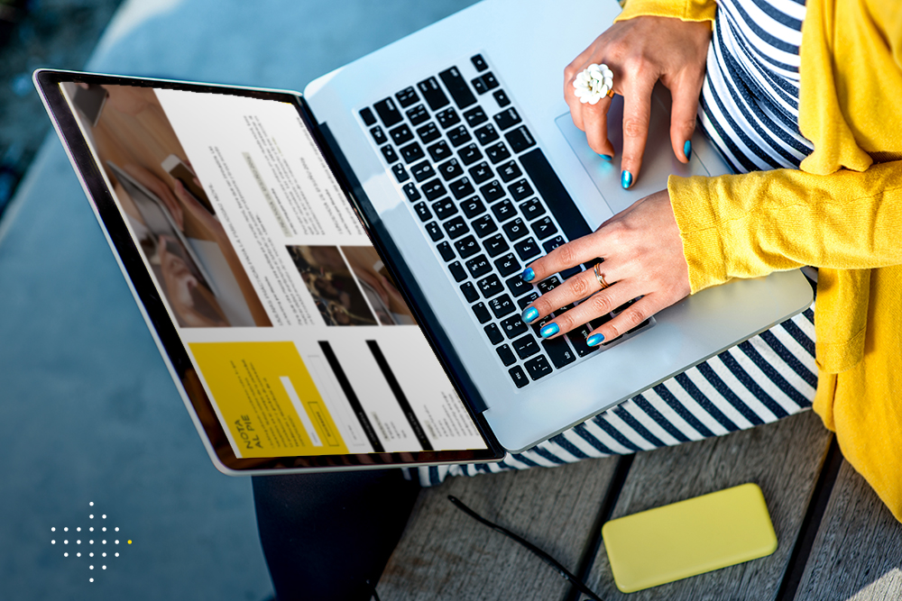 Woman typing on laptop with empty yellow screen sitting on the bench